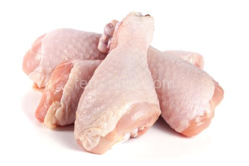 four raw chicken drumsticks isolated on white background